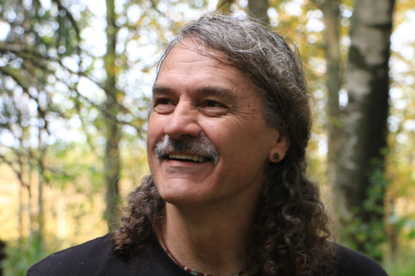 Alan Watson, a middle-aged man with long, curly grey hair and a grey mustache, smiles kindly in a forest.