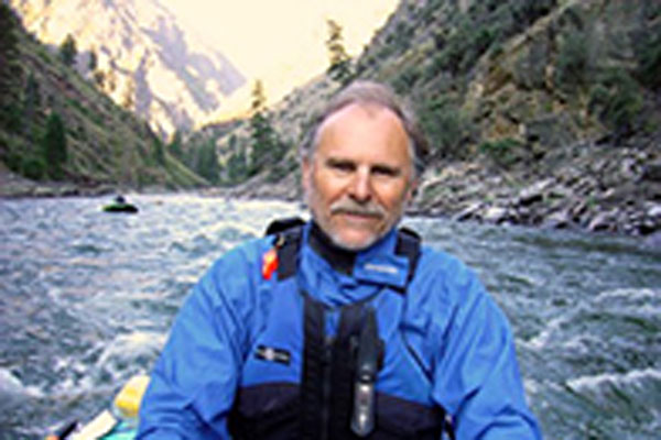 David Cole, an older man with grey hair, rows a kayak on a river.