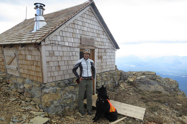 Lisa Holsinger, a young woman with brown hair in braids, stands proudly in front of a cabin on an exceptionally high peak. The valley below is dizzyingly far away. Her black dog sits beside her.