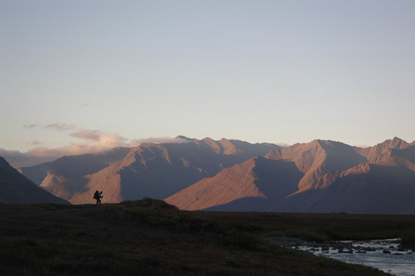 Image of a hiker on a broad landscape with mountains and sky